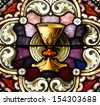Stained glass window depicting a golden chalice and paten - stock photo
