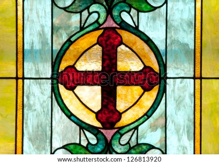 Stained glass window depicting dark red cross in gold circle surrounded by blue and green patterns - stock photo