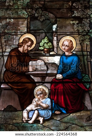 Stained glass window depicting the Holy Family, St. Joseph, Blessed Virgin Mary and the child Jesus - stock photo