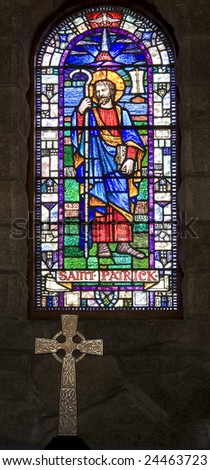 stained glass window of saint patrick with celtic cross in foreground