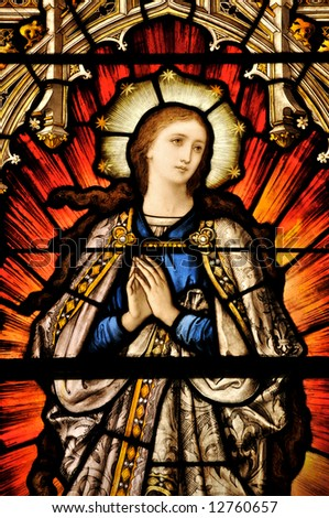 Stained Glass window of St Mary in contemplative prayer - stock photo