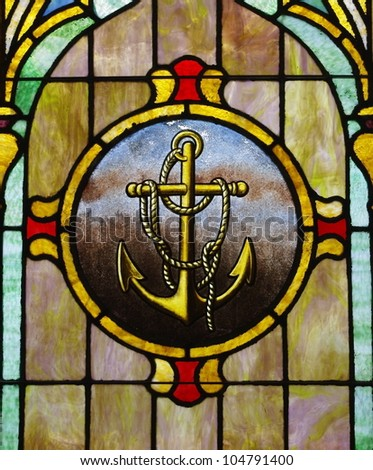 Stained Glass Window with Anchor Image:  Multicolored stained glass window with anchor & rope centered on it's panel - stock photo