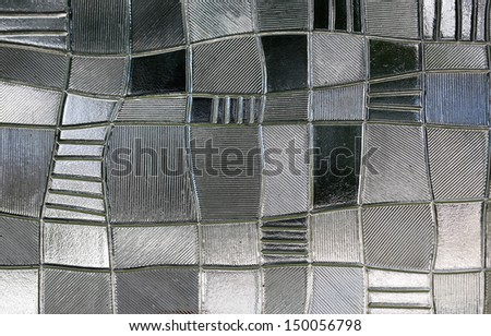 stained glass window with irregular block pattern in a hue of gray, square format
