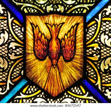 Stained glass window with symbol of Holy Spirit - stock photo