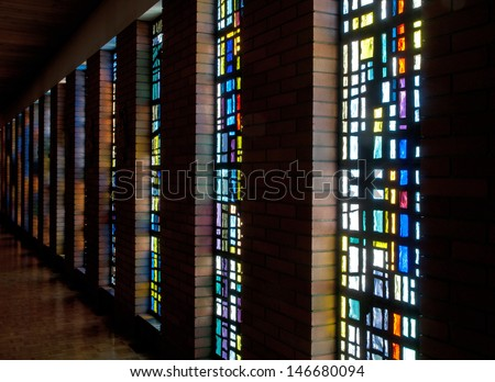 Stained glass windows and their colorful reflections on the brick walls of the church, Saint Benedict's Monastery, Winnipeg, Manitoba, Canada - stock photo