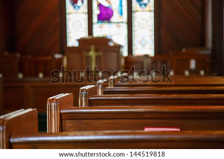 Stained glass windows in small church with wood pews - stock photo