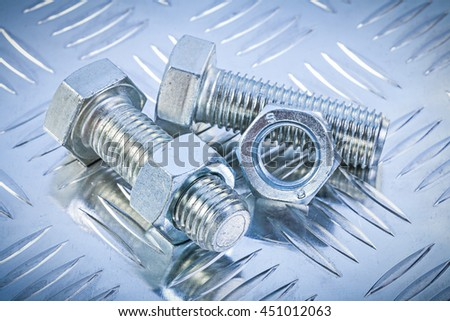 Stainless bolts and construction nuts on grooved metal sheet top view maintenance concept.