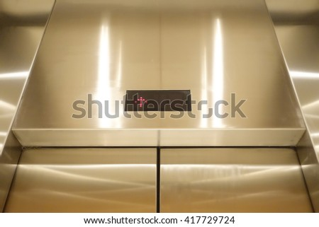 Stainless elevator or lift under yellow light. - stock photo
