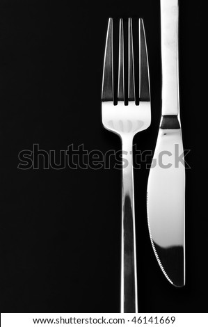 Stainless knife and fork on black background with copy space.
