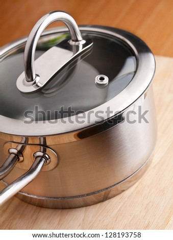 Stainless pan with a glass cover - stock photo