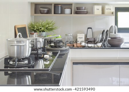 Stainless pots and ceramic ware setting on the counter in the kitchen - stock photo