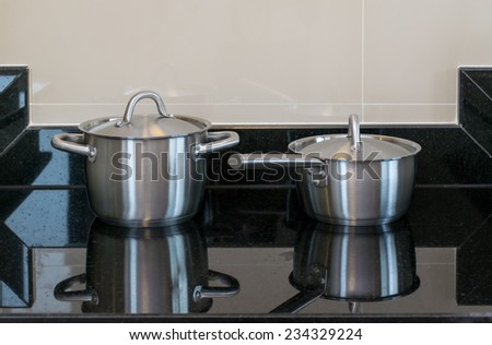 stainless pots in modern kitchen - stock photo