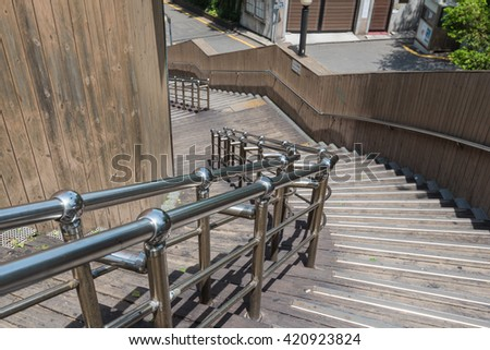 stainless steel banister with wooden staircase - stock photo