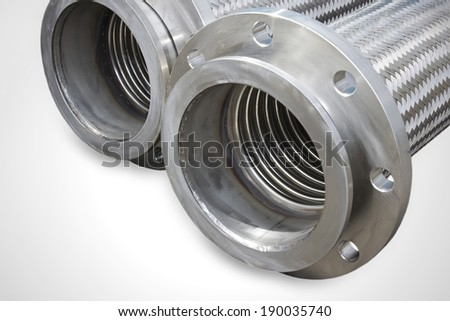 Stainless steel corrugated and braided hoses with flange endings. Metal tubes. - stock photo