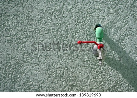 stainless steel drinking fountain on the green wall - stock photo