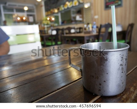 Stainless steel glass with drop of water on wood table - stock photo