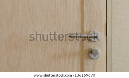 Stainless Steel Handle on light brown wooden door
