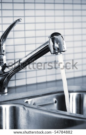 Stainless steel kitchen faucet and sink with running water - stock photo
