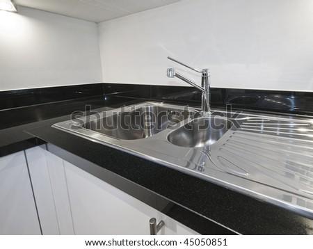 stainless steel kitchen sink detail on black granite worktop - stock photo