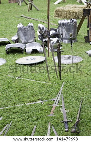 Stainless steel medieval armor in the field, recreation and event - stock photo