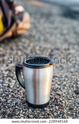 stainless steel mug on the pavement - stock photo