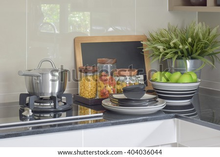 Stainless steel pot and pasta jars on black granite top counter - stock photo