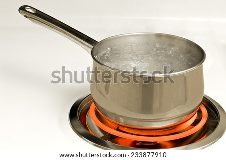 Stainless Steel Pot On Red Hot Electric Burner On Stove - stock photo