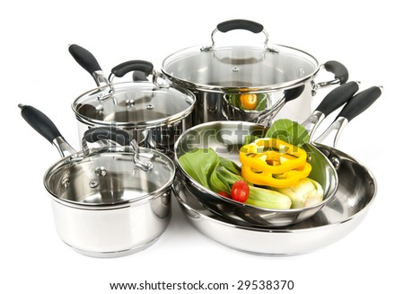 Stainless steel pots and pans isolated on white background with vegetables