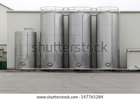 Stainless steel silo for storing bulk materials in factory - stock photo