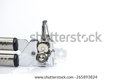 Stainless steel silver metal tin and can opener on empty background. Concept of modern and simplistic kitchen utensil. Slightly de-focused and close-up shot. Copy space. - stock photo
