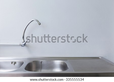 stainless steel sink and faucet in white kitchen room - stock photo