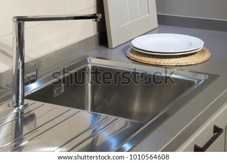 Stainless still kitchen sink, metal mixer and two white ceramic plates