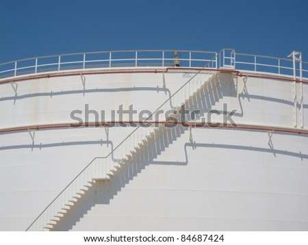 Stair and pipes with shadows at oil tank - stock photo
