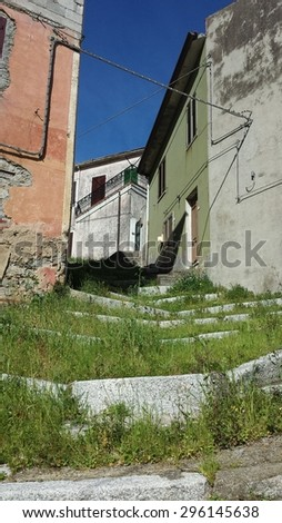 Staircase full of grass in mountain town with abandoned homes