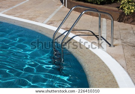 staircase in blue water swiming pool