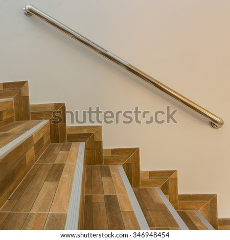 staircase in residential house with stainless steel banister, ceramic floor tiles wood pattern - stock photo