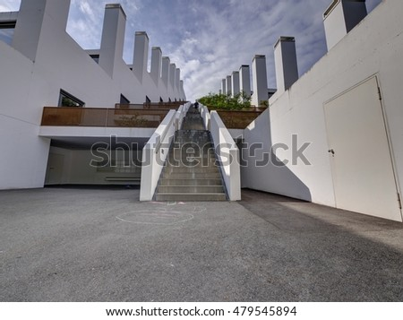 Staircase, stairway up on stepped building, terrace house with big chimney, stack