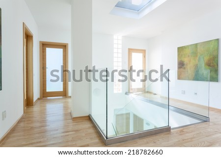Stairs, glass banister and doors in modern hallway on the attic - stock photo