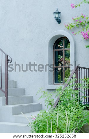 Stairs in the garden with white walls, glass windows, European style.