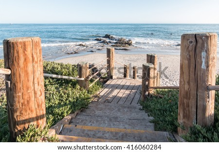 Stairs leading down to the beach and Pacific ocean at Carpinteria State Beach, California.  - stock photo
