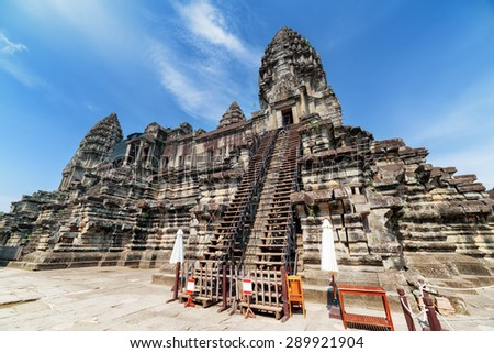 Stairs leading to upper galleries and towers of main Temple Mountain of ancient temple complex Angkor Wat in Siem Reap, Cambodia. Blue sky in background. Angkor Wat is a popular tourist attraction. - stock photo