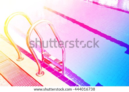 Stairs of the empty swimming pool in university with color filters - stock photo