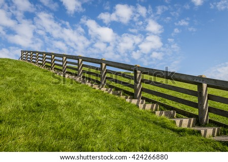 Stairs on a green grass dike in Friesland in the summer in the Netherlands. - stock photo