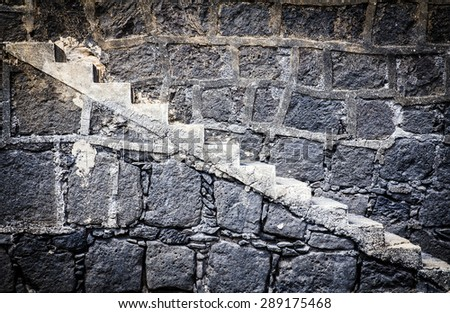 Stairs on a textured wall of stone