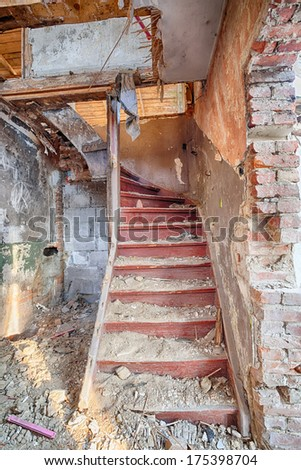 Stairs to the attic of a ruined building - stock photo