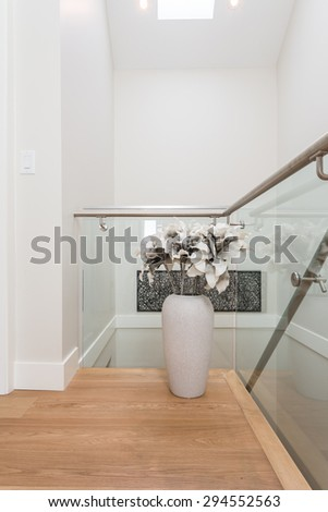 Stairs to the second floor in a luxury house with a flower vase, decoration. Interior design.