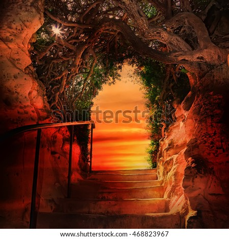 Stairway to sunset. Stone steps leading from underground up to the light through arched exit door. Green branches of an old tree over the arch. Sun patches of light among the leaves. Fantasy