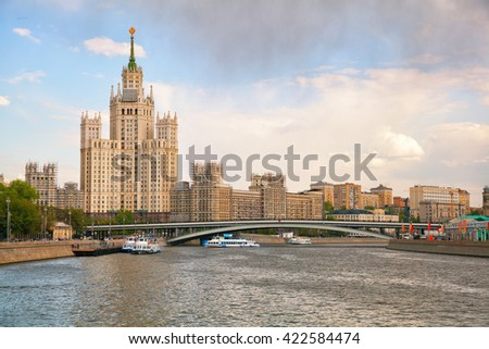 Stalin skyscraper in Moscow, river ships sail on the Moscow river. Cityscape in the center of Moscow, Russia