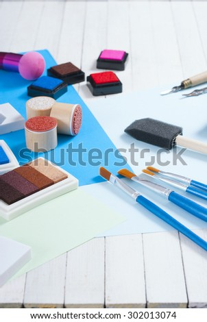 stamp ink pad, lino cutter , papers and rubbers on white wood table