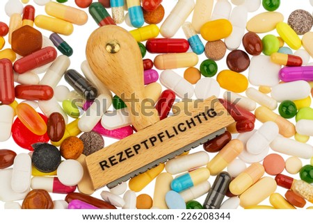 stamp on colorful tablets, symbolic photo for drugs, prescription braids and payment - stock photo